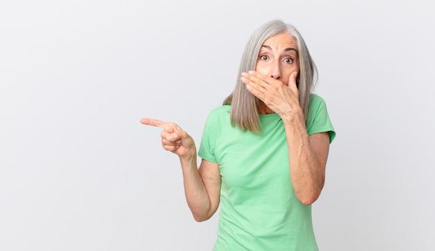 Kobieta w średnim wieku z siwymi włosami zakrywająca usta dłońmi zszokowana i skierowana w bok