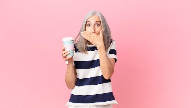 Kobieta w średnim wieku z siwymi włosami zakrywająca usta dłońmi zszokowana i trzymająca pojemnik na kawę na wynos