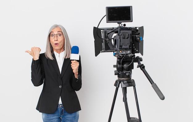 Kobieta w średnim wieku z siwymi włosami, zdumiona z niedowierzaniem i trzymająca mikrofon. koncepcja prezentera telewizyjnego
