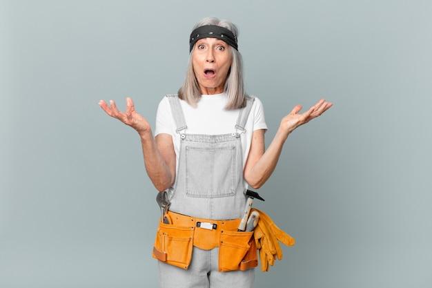 Kobieta w średnim wieku z siwymi włosami zdumiona, zszokowana i zdumiona niewiarygodnym zaskoczeniem, ubrana w strój roboczy i narzędzia. koncepcja sprzątania