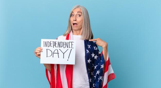 Kobieta w średnim wieku z siwymi włosami, zszokowana i zaskoczona, z szeroko otwartymi ustami, wskazującymi na siebie. koncepcja dnia niepodległości