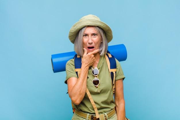 Kobieta w średnim wieku z szeroko otwartymi ustami i oczami i dłońmi na brodzie, czująca się nieprzyjemnie zszokowana, mówiąca co lub wow