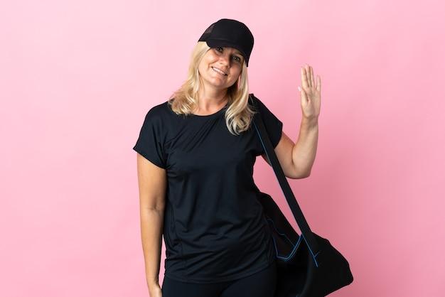 Kobieta w średnim wieku z torbą sportową na białym tle na różowej ścianie, salutując ręką z szczęśliwym wyrazem twarzy