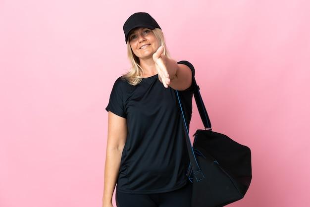 Kobieta w średnim wieku z torbą sportową na różowej ścianie, ściskając ręce za zamknięcie dobrej okazji