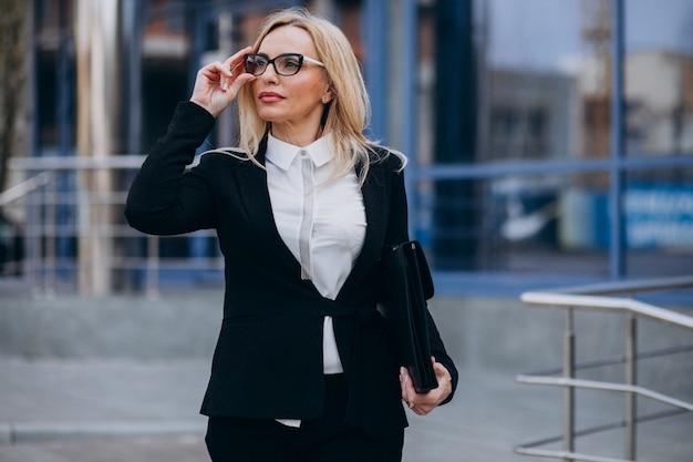 Kobieta w średnim wieku z walizką przez centrum biznesowe