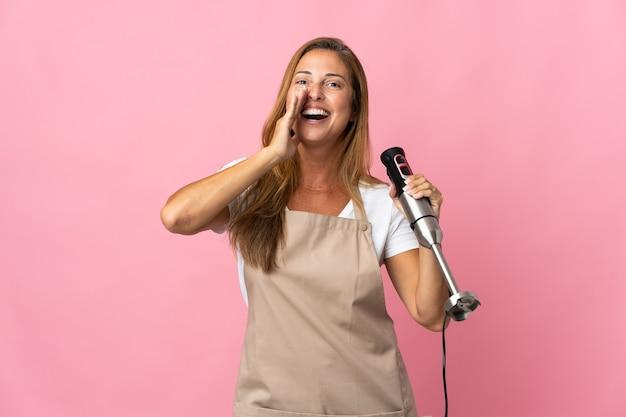 Kobieta w średnim wieku za pomocą ręcznego blendera na różowym tle, krzycząc z szeroko otwartymi ustami