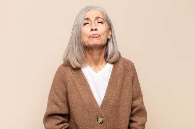 Kobieta w średnim wieku zaciskająca usta ze słodkim, wesołym, radosnym wyrazem twarzy, przesyłająca buziaka