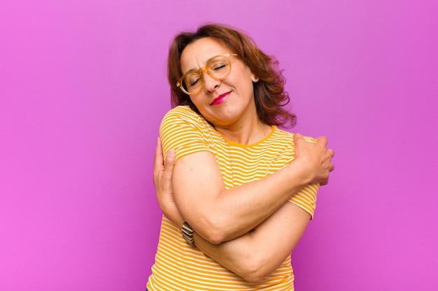 Kobieta w średnim wieku zakochana, uśmiechnięta, przytulająca się i przytulająca, pozostająca samotna, będąca samolubna i egocentryczna wobec fioletowej ściany