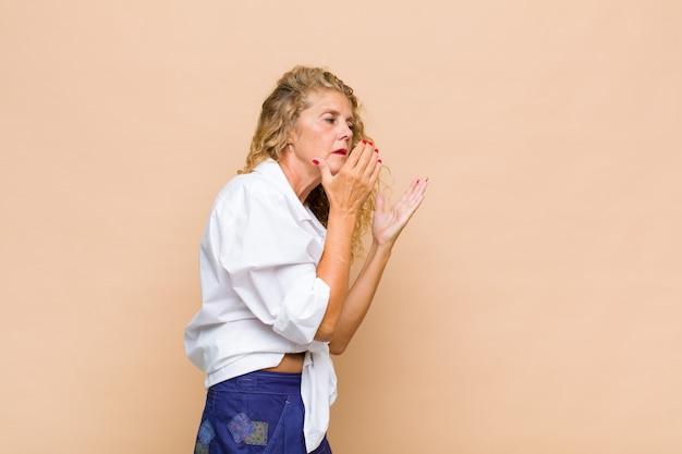 Kobieta w średnim wieku zakrywająca oczy dłońmi ze smutnym, sfrustrowanym spojrzeniem rozpaczy, płacz, widok z boku