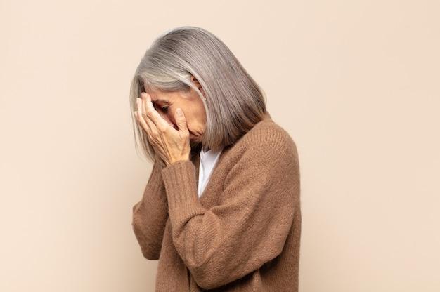 Kobieta w średnim wieku zakrywająca oczy dłońmi ze smutnym, sfrustrowanym wyrazem rozpaczy