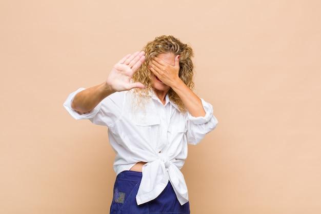 Kobieta w średnim wieku zakrywająca twarz ręką i wyciągająca drugą rękę do przodu, aby zatrzymać się do przodu, odmawiając zdjęć lub zdjęć