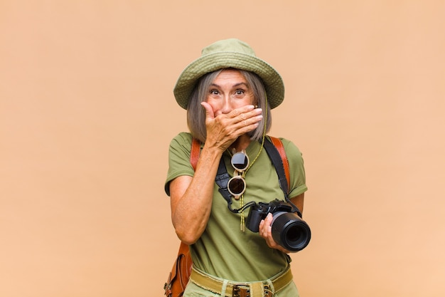 """Kobieta w średnim wieku zakrywająca usta dłońmi z zszokowanym, zaskoczonym wyrazem, dochowująca tajemnicy lub mówiąca """"ups"""""""