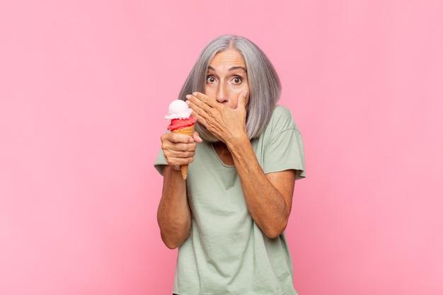 Kobieta w średnim wieku zakrywająca usta rękami w szoku