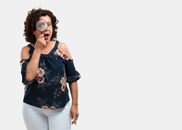 Kobieta w średnim wieku zaskoczona i szeroko otwartymi oczami patrząc przez szkło powiększające, studiując coś, znajdując dowody