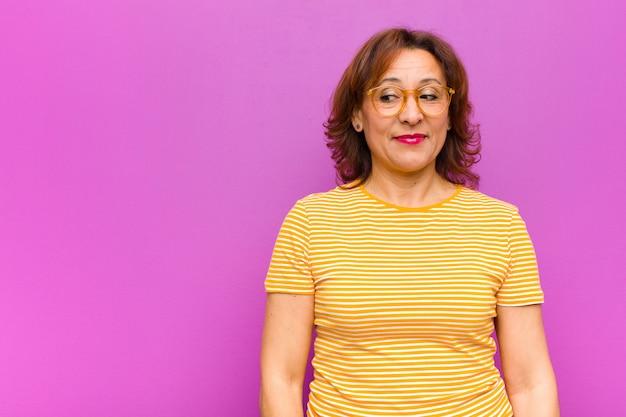 Kobieta w średnim wieku zastanawia się, myśli szczęśliwe myśli i pomysły, marzy, chce skopiować przestrzeń na boku na tle fioletowej ściany