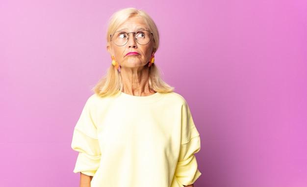 Kobieta w średnim wieku zastanawia się, myśli szczęśliwe myśli i pomysły, marzy na jawie, chce skopiować miejsce na boku