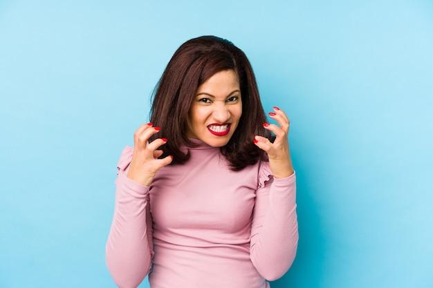 Kobieta w średnim wieku zdenerwowany krzyczy z napiętymi rękami.