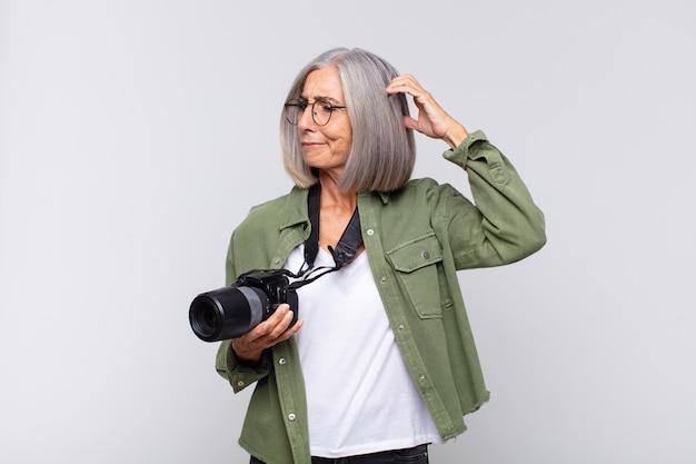 Kobieta w średnim wieku, zdziwiona i zagubiona, drapiąca się po głowie i spoglądająca w bok. koncepcja fotografa