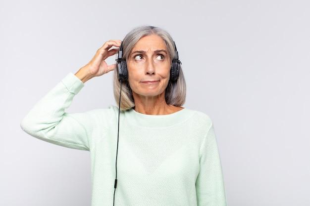 Kobieta w średnim wieku, zdziwiona i zagubiona, drapiąca się po głowie i spoglądająca w bok. koncepcja muzyki