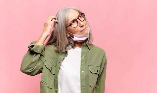 Kobieta w średnim wieku, zdziwiona i zagubiona, drapiąca się po głowie i spoglądająca w bok