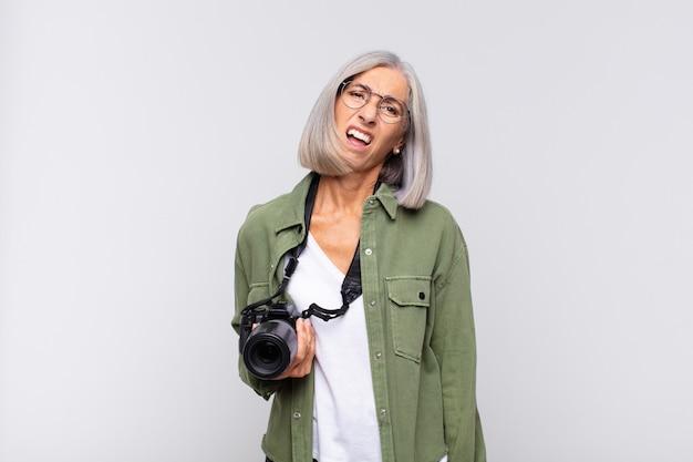 Kobieta w średnim wieku, zdziwiona i zdezorientowana, z głupim, oszołomionym wyrazem twarzy, patrząc na coś nieoczekiwanego. koncepcja fotografa