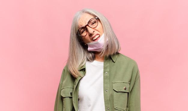 Kobieta w średnim wieku, zdziwiona i zdezorientowana, z głupim, oszołomionym wyrazem twarzy, spoglądająca na coś nieoczekiwanego