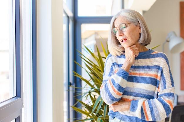 Kobieta w średnim wieku źle się czuje z bólem gardła i objawami grypy, kaszle z zakrytymi ustami