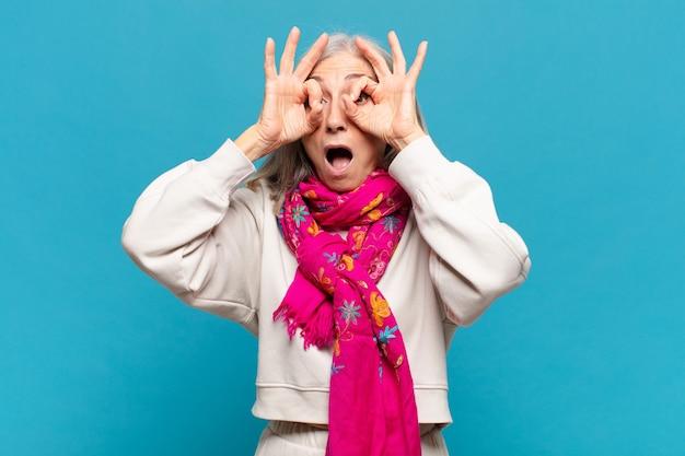 Kobieta w średnim wieku, zszokowana, zdumiona i zdziwiona, trzymająca okulary ze zdumieniem i niedowierzaniem