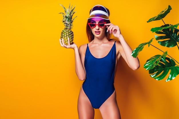 Kobieta w strój kąpielowy gospodarstwa ananasa