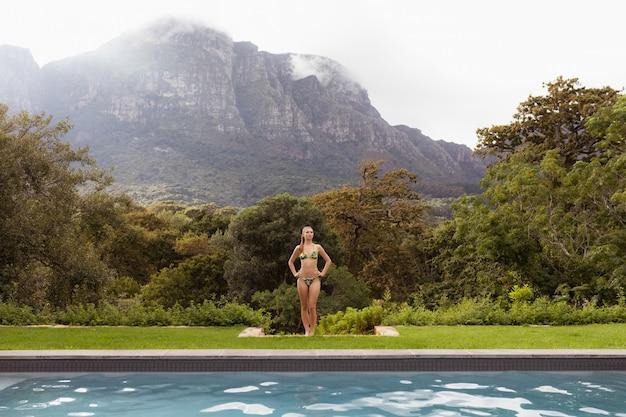 Kobieta w strój kąpielowy stojący z rękami na biodrze w pobliżu basenu