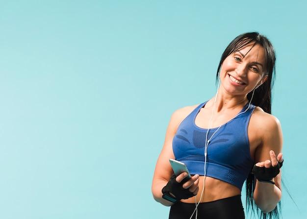 Kobieta w strój siłowni, słuchanie muzyki w słuchawkach