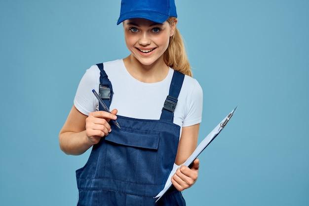 Kobieta w strojach dostawy pozowanie na niebieską ścianę