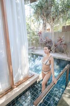 Kobieta w strojach kąpielowych wychodzi z basenu.