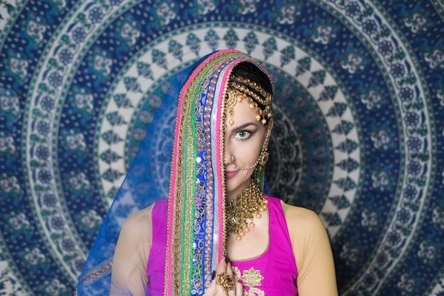 Kobieta w stroju indyjskim z biżuterią i makijażem