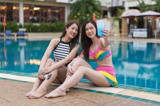 Kobieta w stroju kąpielowym, co selfie zdjęcie na smartphone w basenie