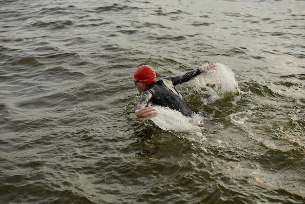 Kobieta w stroju kąpielowym pływająca w stylu kraul w jeziorze podczas zawodów