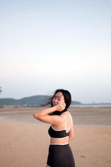 Kobieta w stroju kąpielowym relaksuje się na plaży