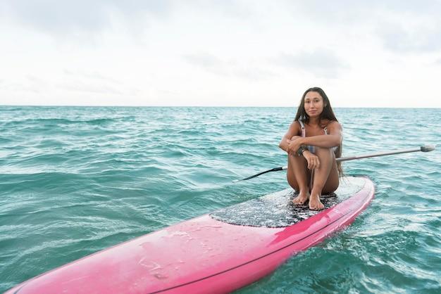 Kobieta w stroju kąpielowym surfuje na hawajach