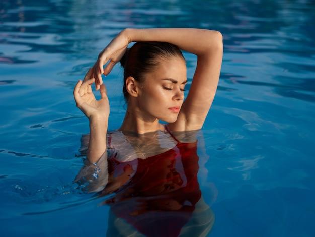 Kobieta w stroju kąpielowym trzyma ręce na głowie z zamkniętymi oczami