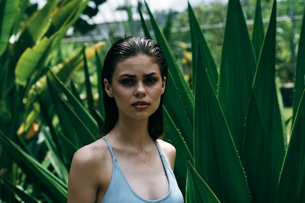 Kobieta w stroju kąpielowym w pobliżu zielonych liści egzotycznych krzewów dżungli