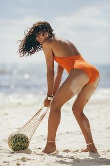 Kobieta w stroju kąpielowym z arbuzem na plaży na zewnątrz