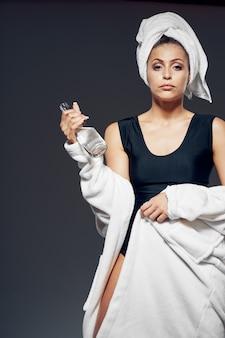 Kobieta w stroju kąpielowym z ręcznikiem na głowie i białą szatą ciemnym tle przycięty widok