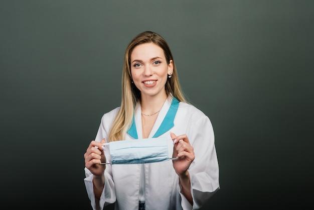 Kobieta w stroju medycznym z maską medyczną w rękach.
