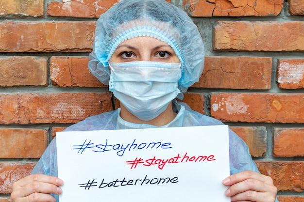 Kobieta w stroju ochronnym z napisem na prześcieradle zostaje w domu