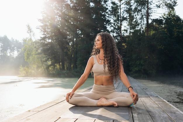 Kobieta w stroju sportowym ćwicząca jogę siedząca na macie w pozycji lotosu jest zaangażowana w medytację