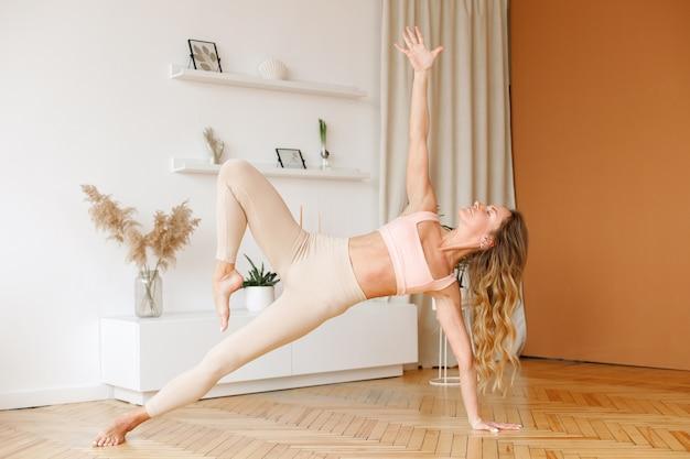 Kobieta w stroju sportowym ćwiczy jogę w domu