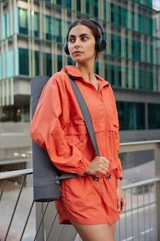 Kobieta w stroju sportowym idąca na zajęcia jogi z instruktorem wygląda w zamyśleniu na pozostawione pozy na tle nowoczesnego budynku ze szkła