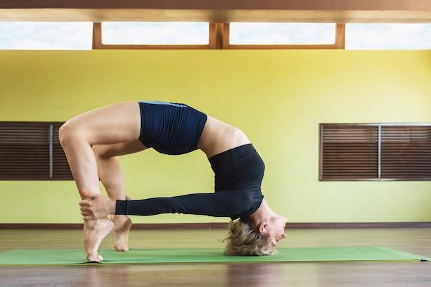 Kobieta w stroju sportowym uprawiająca jogę wykonuje dvipada pithasana pozę do połowy mostu ze staniem na głowie