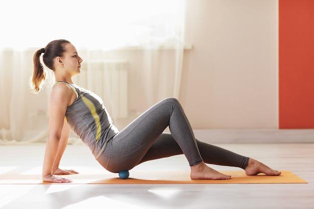 Kobieta w stroju sportowym wykonuje masaż mięśniowo-powięziowy mięśni pośladkowych