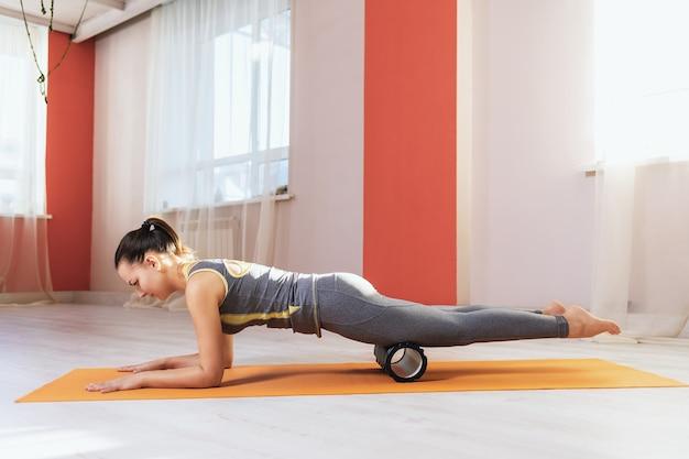 Kobieta w stroju sportowym wykonuje na macie na siłowni masaż mięśniowo-powięziowy mięśni ud rolką